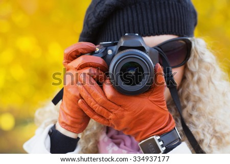 Young lady taking a portrait picture over yellow autumnal background - stock photo