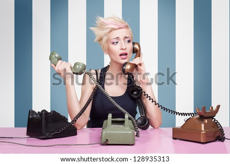 young lady trying to answer the phones on striped background - stock photo