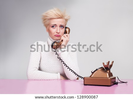 young lady wearing white turtleneck sweater getting bad news on the phone and crying - stock photo