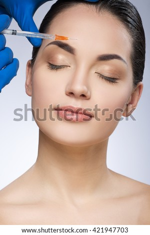 Young lady with closed eyes. Head turned aside. Forehead operated by plastic surgeon. Beauty injection by doctor in blue gloves. Beauty portrait, head and shoulders. Indoor, studio - stock photo