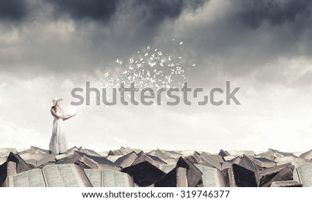 Young lady with laptop standing on pile of books - stock photo