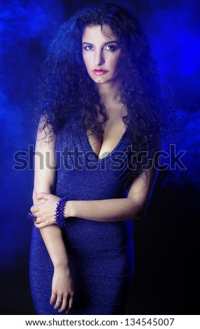 Young lady with long dark hair posing in smoke - stock photo