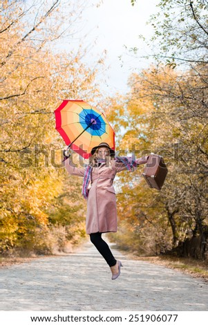 Young lady with rainbow colorful umbrella and suitcase jumping and looking at camera over autumn road - stock photo