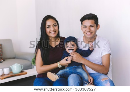Young latin couple with a six month baby sharing a happy moment in their home - stock photo