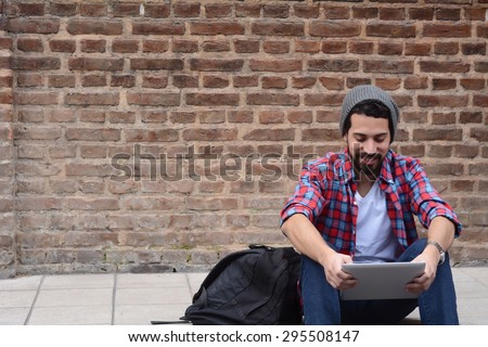 Young latin man using a tablet, with red headphones. - stock photo