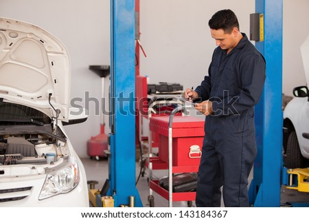 Young Latin mechanic using a checklist for a car inspection at an auto shop - stock photo