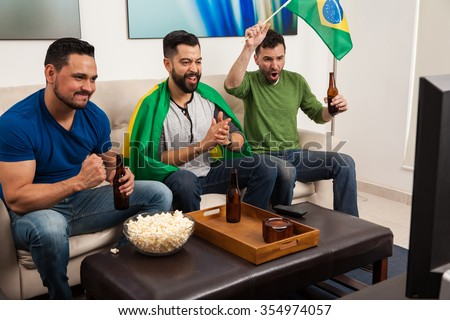 Young Latin men cheering for Brazil on TV while hanging out and drinking some beer at home - stock photo