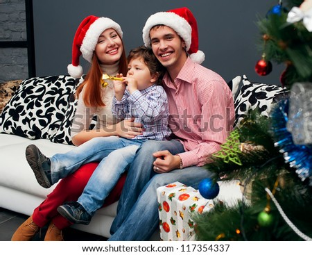 Young laughing family home with spruce on crastmas - stock photo