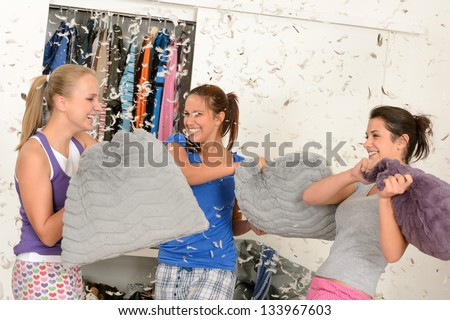 Young laughing girls during pillow fight with flying feathers - stock photo