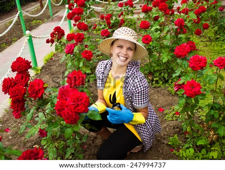 Young laughing woman gardening with roses in garden - stock photo