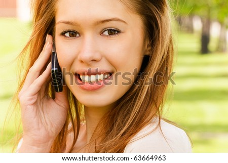 Young laughing woman talks by mobile phone in city park. - stock photo