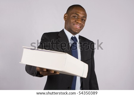 Young lawyer or business man giving you a big book - stock photo