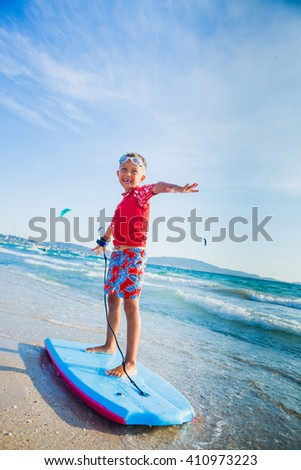 Young little boy learning to surf board - stock photo