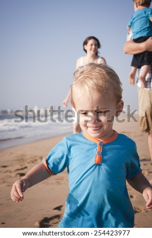 Young little boy running along beach ahead of family - stock photo