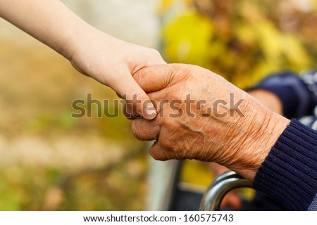 Young little boy shaking hands with old man. - stock photo