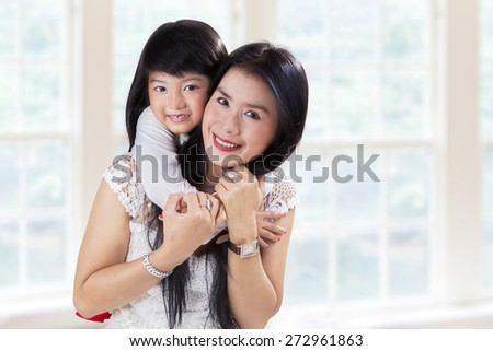 Young little girl hugging her mother from the back at home - stock photo