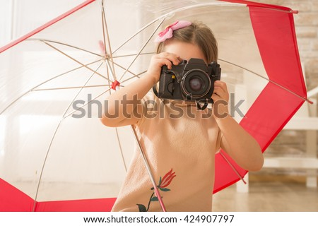 Young little girl photographer with old vintage photo camera taking picture sitting under umbrella, indoor shot. Beautiful girl using vintage photo camera. Children's play. Art or creativity concept. - stock photo