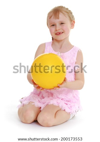 young little girl sitting on the floor and holding a yellow ball. Isolated on white background - stock photo