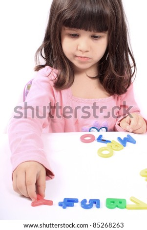 Young little preschool girl with funny expression playing with letters and numbers - stock photo