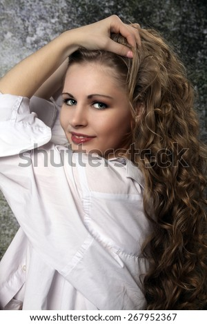 Young long-haired curly blonde woman presented beautiful natural long curly blond hair - stock photo