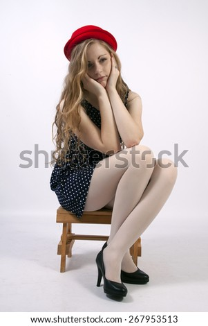 Young long-haired curly blonde woman sitting sad - stock photo
