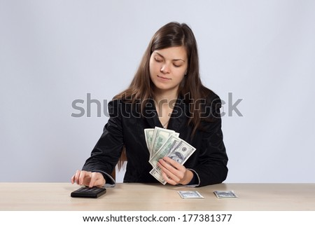 Young long-haired woman sitting at a desk and using a calculator counts dollars - stock photo