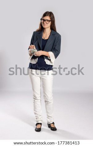 Young long-haired woman stands in hands counts dollars - stock photo