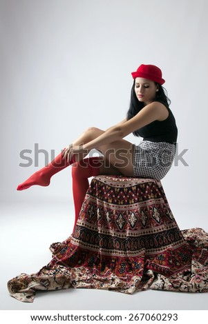 Young long-haired woman with red hat sits on a chair and gives a red stocking - stock photo