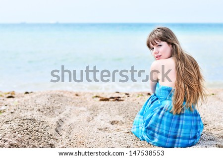 young longhaired woman sitting alone at the beach  - stock photo