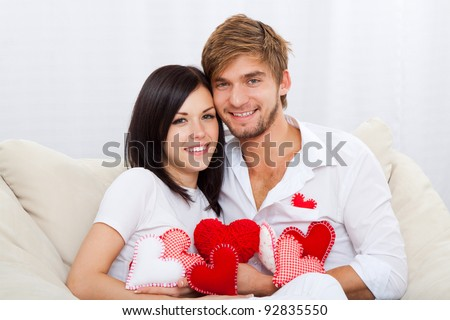 young love couple holding lot of red valentine's heart together sitting on couch at home, excited happy smile looking at camera, hug, valentine day love concept - stock photo
