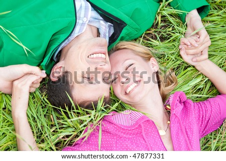 Young love couple lay on the green grass outdoors. - stock photo