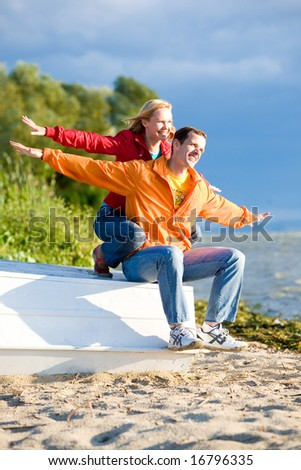 Young love Couple sit on boat on bank of river - stock photo