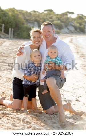young lovely and beautiful wife and husband holding little daughter and baby boy posing on beach sand sea shore smiling happy in family love and Summer vacation concept - stock photo