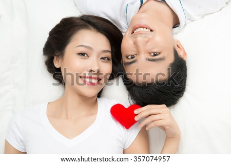 young lovely asian couple holding red heart together lying in a bed, happy smile looking at camera, valentine day love concept - stock photo
