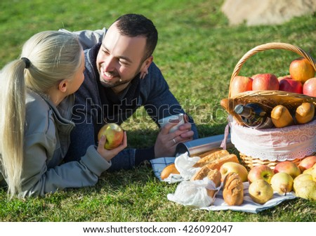 Young lovely couple chatting as having picnic in sunny day  - stock photo