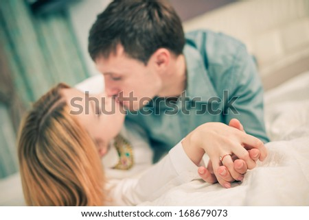 young lovely couple kissing on a bed - stock photo