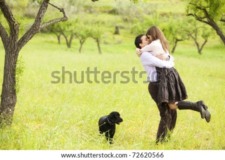 Young lovely couple kissing under nature. - stock photo