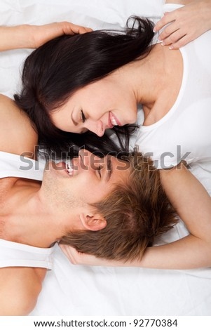 young lovely couple lying in a bed, happy smile looking to each other, top view - stock photo