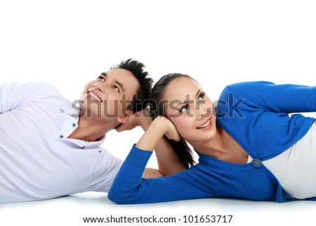 young lovely couple lying on the floor looking up to the copy space - stock photo