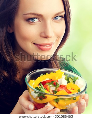Young lovely smiling brunette woman with salad, outdoor - stock photo