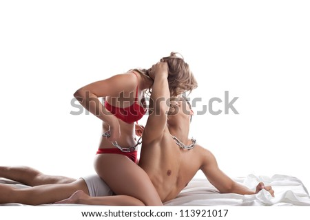 Young lovers play in bed with chain - sexual games - stock photo
