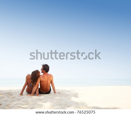 Young lovers sitting on warm beach at sunny day and enjoying each other - stock photo
