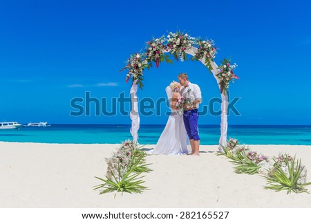 young loving couple, bride and groom, on their wedding day on wedding setup, arch, venue background, beach wedding in tropics - stock photo