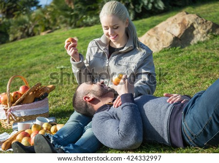 Young loving couple chatting as having picnic in sunny day  - stock photo