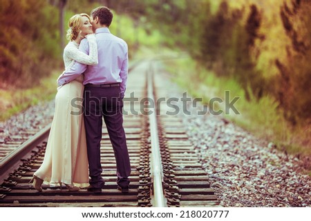 young loving couple having a walk on the railway in summertime - stock photo