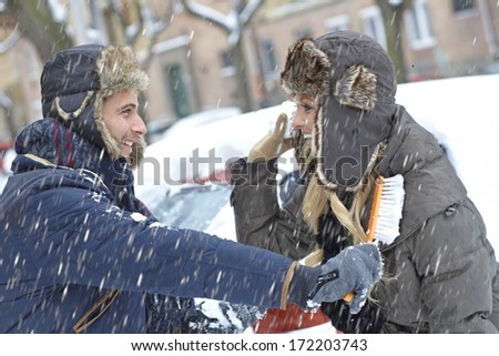 Young loving couple having fun in snowfall, brushing off car, throwing snowball. - stock photo
