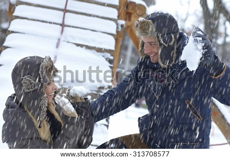 Young loving couple having fun, throwing snowball, laughing. - stock photo