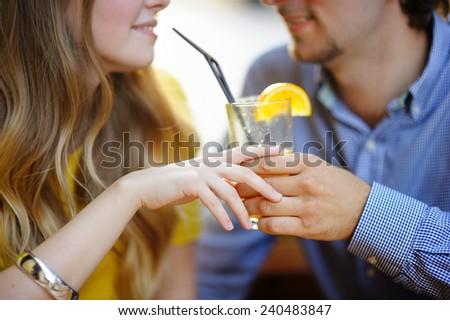 Young loving couple holding glass of orange juice - stock photo