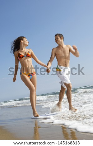 Young loving couple holding hands while running in surf at beach - stock photo