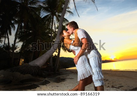 young loving couple hugging on beach at sunset - stock photo